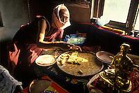 Nepal, Kathmandu. Tibetan lama filling staue with prayers. He wears a mask so not to contaminate them.