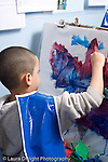 Educaton preschool 4-5 year olds art activtiy painting boy wearing smock at easel painting with brush  vertical