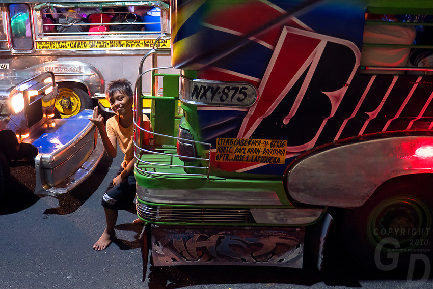General life and environs in the Malate, Manila area and Manila Bay, Philippines. Jeepney at night and a boy is jumping out in the traffic. Manila, Philippines