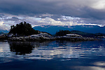 Blackfish Sound islets shimmer in evening light as a storm passes, near Stubbs Island, Broughton Strait, and Telegraph Cove on Vancouver Island, Canada.  The area contains numerous marine parks popular with kayakers and whale watchers.