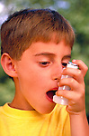 young boy using inhaler