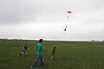 CHAD PILSTER •Hays Daily News<br /> <br /> (left to right) Nicholas Newell, 12, Kwinter Hartsthorn, 17, and Xander Palmberg, 9, chase Hartsthorn's rocket as it parachutes down on Saturday, August 3, 2013, during the 4-H and Open Class Rocket launch as part of the Rush County Fair at the Rush County Airport in La Crosse, Kansas.