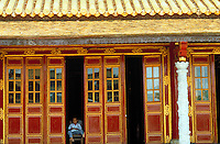 A young boy reads in the doorway to a temple in the ancient city of Hue, Vietnam. Hue, Vietnam.