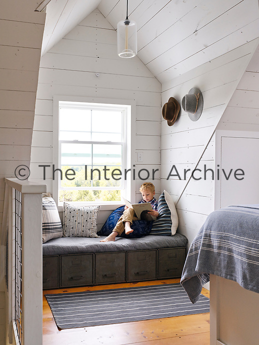 The upstairs loft houses the white, wood panelled master bedroom. The room is light and airy with its vaulted ceiling and the simple blue and white theme gives the space a cool feel. A window seat set in a window recess, has drawers below for extra storage.