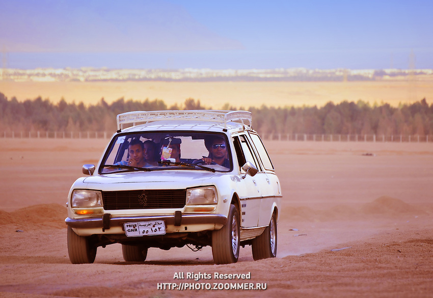 Arabs in old car on the road in desert in Egypt