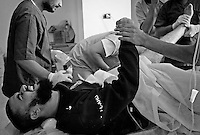 Anti-Gaddafi fighter being treated for leg wounds at a field clinic west of Sirte, Libya.