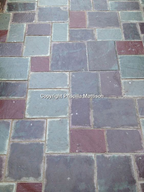 The subdued colors of a flagstone walkway create an abstract design.