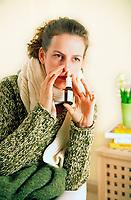 Young woman using nasal spray