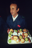 Switzerland. Canton Lucerne. Lunch time in the Sonnenberg tunnel in Lucerne during the largest civil defense exercise ever held in the country. A man carries a tray with plastic plates. A piece of bread, a pork sausage, a melted cheese in aluminium foil and a green apple. From 16 to 21 November 1987, almost 1200 men and women converted a motorway tunnel into perhaps the world's largest bunker structure. The civil protectors had to prove during the exercise «Ameise » ( Ants in english) that in an emergency more than 20,000 inhabitants of the city of Lucerne could survive here in the mountain for two weeks. The Sonnenberg Tunnel is a 1,550 m  long motorway tunnel, constructed between 1971 and 1976. At its completion it was also the world's largest civilian nuclear fallout shelter, designed to protect 20,000 civilians in the eventuality of war or disaster. Based on a federal law from 1963, Switzerland aims to provide nuclear fallout shelters for the entire population of the country. The construction of a new tunnel near an urban centre was seen as an opportunity to provide shelter space for a large number of people at the same time. The giant bunker was built between 1970 and 1976 at a cost of 40 million Swiss francs. The shelter consisted of the two motorway tunnels (one per direction of travel), each capable of holding 10,000 people in 64 person subdivisions. A seven story cavern between the tunnels contained shelter infrastructure including a command post, an emergency hospital, a radio studio, a telephone centre, prison cells and ventilation machines. The shelter was designed to withstand the blast from a 1 megaton nuclear explosion 1 kilometer away. The blast doors at the tunnel portals are 1.5 meters thick and weigh 350 tons. The logistical problems of maintaining a population of 20,000 in close confines were not thoroughly explored, and testing the installation was difficult because it required closing the motorway and rerouting the usual traffic. The only l