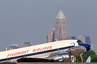 A jet takes off against the Charlotte skyline in the background, at Charlotte-Douglas International Airport in Charlotte, North Carolina. Charlotte-based photographer has other images of transportation, airplanes on runways (and taking off and landing) and interior/exterior airport images of Charlotte-Douglas Intl Airport in portfolio.