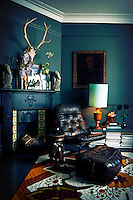 A retro black leather chair pouffe are placed in front of a traditional Victorian fireplae in a blue sitting room. A lamp sits on a sideboard and a floral pattern rug completes the retro feel.