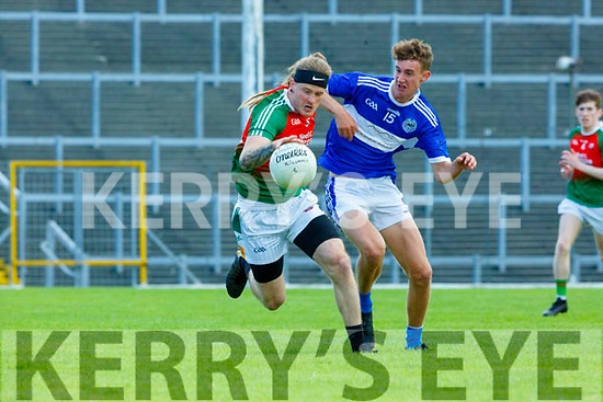 Enda O'Sullivan Kilcummin on the hop past Colin Crowley Templenoe during the relegation play off final in Fitzgerald Stadium on Sunday