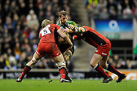 Chris Robshaw of Harlequins is tackled by George Kruis (left) and Carlos Nieto of Saracens during the Aviva Premiership match between Harlequins and Saracens at Twickenham on Tuesday 27 December 2011 (Photo by Rob Munro)