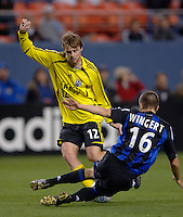 Colorado defender Chris Wingert tackles the ball away from Columbus midfielder Eddie Gaven at Denver's Invesco Field at Mile High Stadium, April 8, 2006.