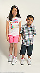 7 year old boy and 11 year old sister portrait full length white background