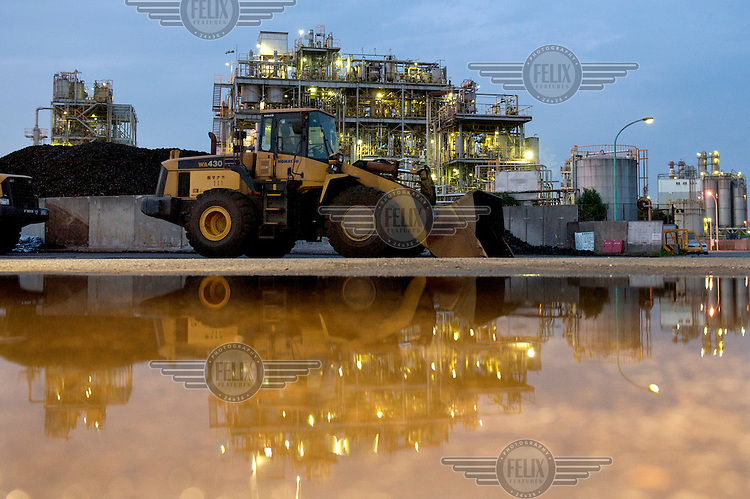 Construction vehicles and industrial buildings reflected in a puddle in the Keihin Industrial Area.