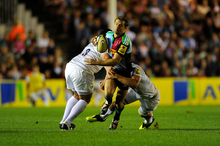 Nick Evans of Harlequins is tackled by Kieran Longbottom (left) and Alistair Hargreaves of Saracens during the Premiership Rugby Round 2 match between Harlequins and Saracens at The Twickenham Stoop on Friday 12th September 2014 (Photo by Rob Munro)