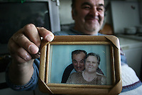 """SERBIA, Belgrade, Jan. 18, 2007..Milan Pjevalica  (60) refugee from Croatia, Knin holds a picture showing his wife and himself in his room in a refugee camp """"Krnjaca"""" near Belgrade..© Djordje Jovanovic /EST&OST"""