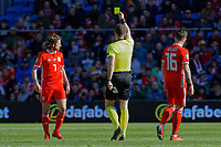 Joe Allen of Wales (L) is shown a yellow card by referee Felix Zwayer during the UEFA EURO 2020 Qualifier match between Wales and Slovakia at the Cardiff City Stadium, Cardiff, Wales, UK. Sunday 24 March 2019