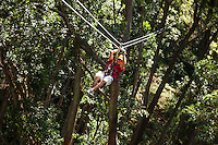 Man Zip-lining through the air and rainforest with Kohala Ziplining in North Kohala on the Big Island.