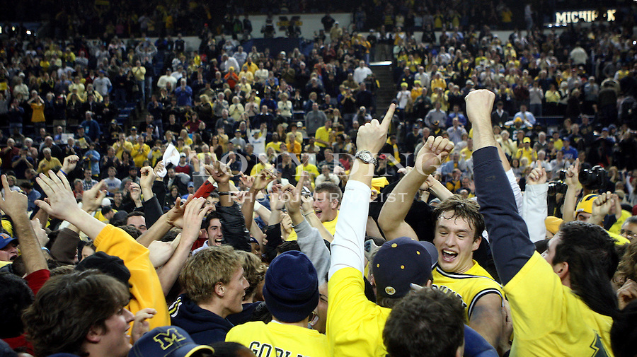 Michigan guard Zack Novak, center right, celebrates with Michigan student fans after an NCAA college basketball game with Duke, Saturday, Dec. 6, 2008, in Ann Arbor, Mich. Michigan upset No. 4th ranked Duke 81-73. (AP Photo/Tony Ding)