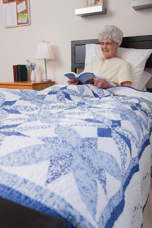 USA, Illinois, Metamora, Senior woman reading book in bed