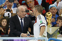 FIFA President Sepp Blatter and Bastian Schweinsteiger of Germany shake hands near the World Cup trophy