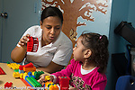 Education Preschool 3 year olds female teacher talking and playing with girl, using colored plastic bricks (duplo)