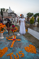 Mexico, Mixquic. Day of the Dead, Dia de los Muertos. Church of San Andres Apostol. People decorating graves. Girl dressed in costume.