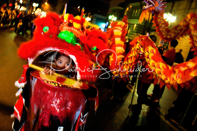 A child steers the head of a Chinese dragon in a parade during First Night Charlotte 2010. The family-friendly public event (no alcohol allowed) is an annual cultural New Year's Eve celebration held in downtown / uptown / Charlotte center city. Charlotte First Night - An Imagination Celebration brought together artists, musicians, dancers and more from across the country. The New Year's event is organized by Charlotte Center City Partners, which facilitates and promotes the economic and cultural development of this North Carolina urban core.