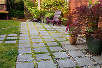 Permeable patio with concrete aggregate pavers for rainwater drainage and groundwater  capture in backyard garden