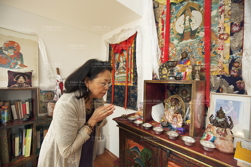 """Switzerland. Canton Aargau. Rüfenah. Yangchen Büchli prays at home. A buddhist altar and a picture of the Dalai Lama. The swiss tibetan woman is an Aeschimann's child who arrived 50 years ago in Switzerland to receive custody on a private initiative by an influential Swiss industrialist, Charles Aeschimann. In 1962, Charles Aeschimann agreed with the Dalai Lama to take 200 children and place them in Swiss foster homes and give them a chance for a better life and a good education. Most of the children still had parents in exile or in Tibet, just a few were orphans. The 14th and current Dalai Lama is Tenzin Gyatso, recognized since 1950. He is the current Dalai Lama, as well as the longest-lived incumbent, well known for his lifelong advocacy for Tibetans inside and outside Tibet. Dalai Lamas are amongst the head monks of the Gelug school, the newest of the schools of Tibetan Buddhism. The Dalai Lama, also called """" Ocean of Wisdom"""" is considered as the incarnation of Chenresi, the Bodhisattva of compassion who is also the protective deity of Tibet. 25.02.2015 © 2015 Didier Ruef"""