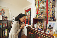 "Switzerland. Canton Aargau. Rüfenah. Yangchen Büchli prays at home. A buddhist altar and a picture of the Dalai Lama. The swiss tibetan woman is an Aeschimann's child who arrived 50 years ago in Switzerland to receive custody on a private initiative by an influential Swiss industrialist, Charles Aeschimann. In 1962, Charles Aeschimann agreed with the Dalai Lama to take 200 children and place them in Swiss foster homes and give them a chance for a better life and a good education. Most of the children still had parents in exile or in Tibet, just a few were orphans. The 14th and current Dalai Lama is Tenzin Gyatso, recognized since 1950. He is the current Dalai Lama, as well as the longest-lived incumbent, well known for his lifelong advocacy for Tibetans inside and outside Tibet. Dalai Lamas are amongst the head monks of the Gelug school, the newest of the schools of Tibetan Buddhism. The Dalai Lama, also called "" Ocean of Wisdom"" is considered as the incarnation of Chenresi, the Bodhisattva of compassion who is also the protective deity of Tibet. 25.02.2015 © 2015 Didier Ruef"