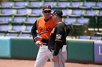 FCL Orioles Orange manager Kevin Bradshaw (25) talks with Gera Alvarez (10) during a game against the FCL Pirates Gold on August 9, 2021 at Ed Smith Stadium in Sarasota, Florida.  (Mike Janes/Four Seam Images)
