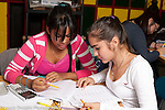 Education high school classroom  two female students working together on mathematics problem