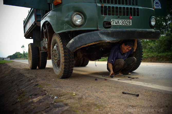 A truck driver repairs a broken down Soviet truck along the Ho Chi Minh Highway inside the former DMZ on 23 February 2010 in Vietnam.