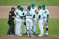 Charlotte 49ers head coach Robert Woodard (20) has a chat on the mound with starting pitcher Hale Sims (43) and the entire infield during the game against the Appalachian State Mountaineers at Atrium Health Ballpark on March 23, 2021 in Kannapolis, North Carolina. (Brian Westerholt/Four Seam Images)