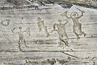 Petroglyph, rock carving, of a group of warriors one  wearing a helmet and carrying a sword and shield. Carved by the ancient Camuni people in the iron age between 1000-1600 BC. Rock no 24,  Foppi di Nadro, Riserva Naturale Incisioni Rupestri di Ceto, Cimbergo e Paspardo, Capo di Ponti, Valcamonica (Val Camonica), Lombardy plain, Italy