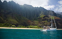 Cruising sailboat anchored off of Kalalau Beach on Kauai's Na Pali coast