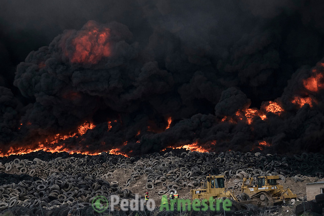 Tyres burn in an uncontrolled dump near the town of Sesena, after a fire broke out early on May 13, 2016. A huge waste ground near Madrid where millions of tyres have been dumped was on fire today, releasing a thick black cloud of toxic fumes that officials worry could harm residents nearby.  © Pedro ARMESTRE