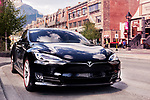 Black 2017 Tesla Model S luxury electric car parked on a city street in Banff, Alberta, Canada. Image © MaximImages, License at https://www.maximimages.com