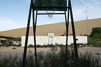 Sand dunes tower over a basketball court. Watermelons are a fruit that demand high amounts of water for growth subsequently contributing to the loss of water in the local ecosystem. Desertification is the process by which fertile land becomes desert, typically as a result of drought, deforestation, or inappropriate agriculture. Dunhuang, Gansu Province. China
