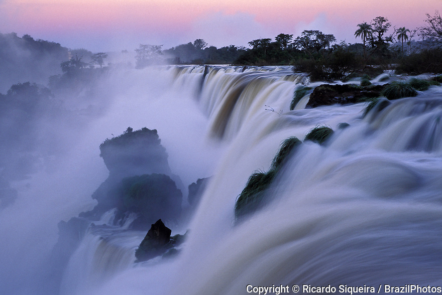 Iguazu Falls, located on the border of the Brazilian State of Parana and the Argentine Province of Misiones. The waterfall system consists of 275 falls along 2.7 kilometres (1.7 mi) of the Iguazu River. Some of the individual falls are up to 82 metres (269 ft) in height, though the majority are about 64 metres (210 ft). Legend has it that a god planned to marry a beautiful woman named Naipi, who fled with her mortal lover Taroba in a canoe. In rage the god sliced the river, creating the waterfalls and condemning the lovers to an eternal fall.