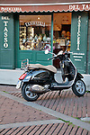 A black vespa in front of a pastry shop in the Piazza Vecchia in Bergamo, Italy