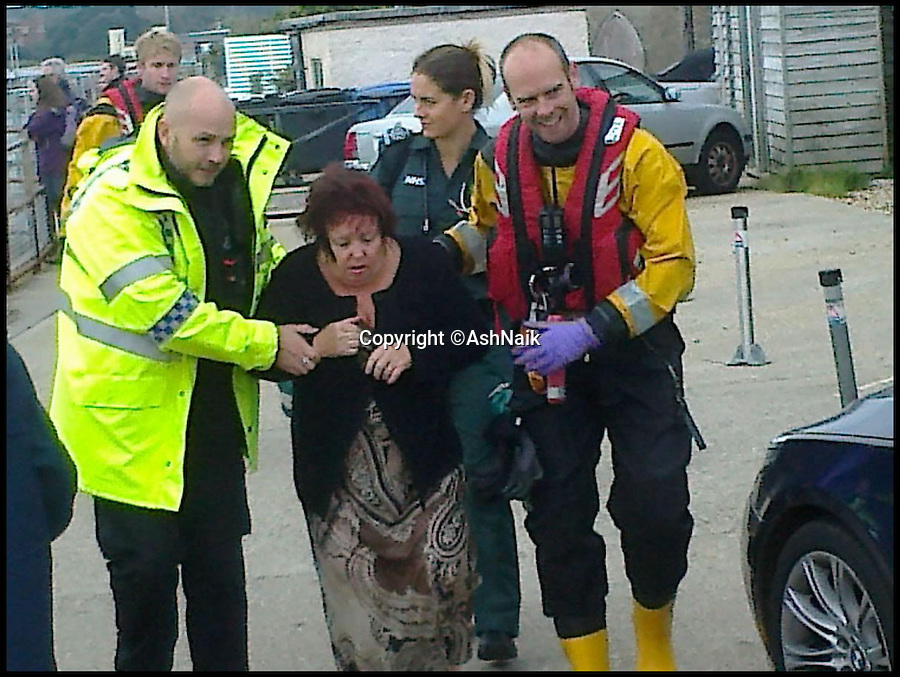 BNPS.co.uk (01202 558833)<br /> Pic: AshNaik/BNPS<br /> <br /> ***Please Use Full Byline***<br /> <br /> The lady being guided away by RNLI workers. <br /> <br /> An elderly woman has today been rescued from her sunken car after she 'deliberately' drove into a harbour in front of stunned <br /> day-trippers.<br /> <br /> The motorist, aged in her 70s, wound down both windows of her Volkswagen Golf before speeding down a ferry slipway and into the water.<br /> <br /> As the silver car was swept 100 yards out to sea by the fast tide the woman sat motionless in the flooded driver's seat, ignoring cries from witnesses on the quayside to get out.<br /> <br /> A brave crew member of a passing fishing boat then dived into the water and pulled the woman free just moments before her vehicle completely sank.