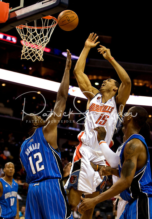 Charlotte Bobcats center Ryan Hollins (15) against Orlando Magic center Dwight Howard (12) during an NBA basketball game  at Time Warner Cable Arena in Charlotte, NC.