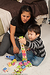 Two year old toddler boy with mother building with alphabet blocks