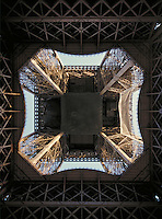 Looking straight up inside the Eiffel Tower in Paris, France. landmark, ornate architecture. Paris, France.
