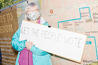 """A crowd gathers in Boston Common for the 2020 Women's March protest in opposition to the re-election of US president Donald Trump in Boston, Massachusetts, on Sat., Oct. 17, 2020.<br /> The sign here reads """"Let the people vote."""""""
