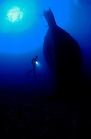 The silhouette of diver (MR) and the wreck of the Mahi off the western side of the island of Oahu, Hawaii underwater sunken shipwreck vessel diving sport explore diving scuba